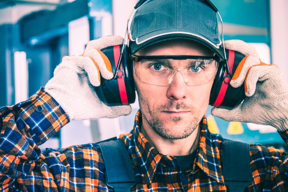 pracownik fabryki z okularami ochronnymi i sluchawkami ochronnymi