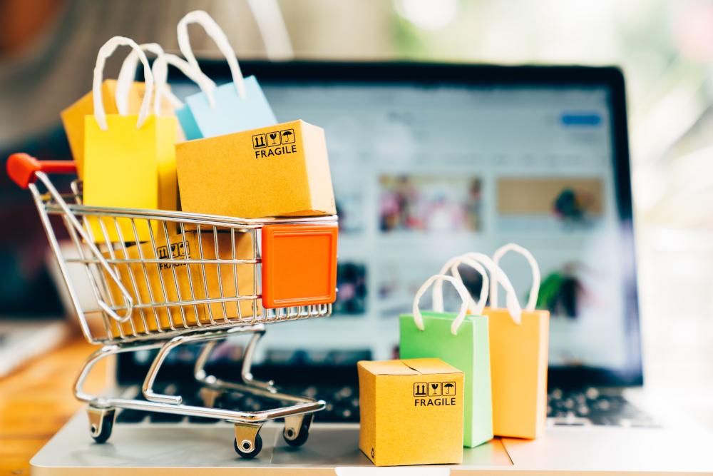 produkty zapakowane w małym wózku na zakupy w tle znajduje się laptop