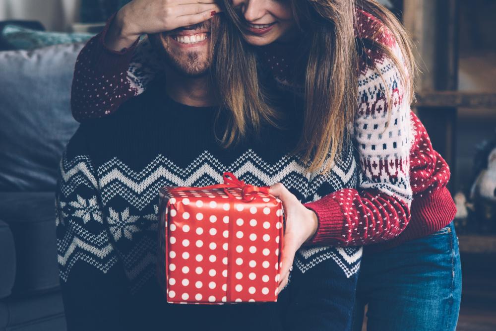 kobieta wręczająca prezent swojemu mężczyźnie