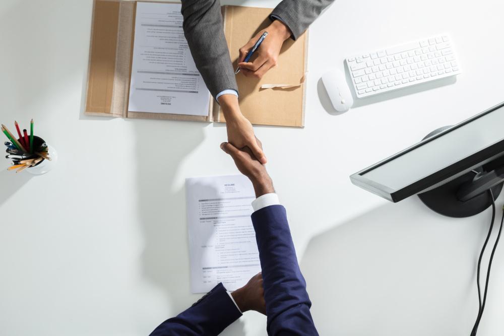 dwóch mężczyzn podających sobie dłonie nad biurkiem