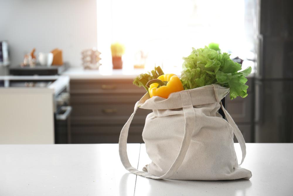 zakupy na stole w kuchni zapakowane w materiałową torbę
