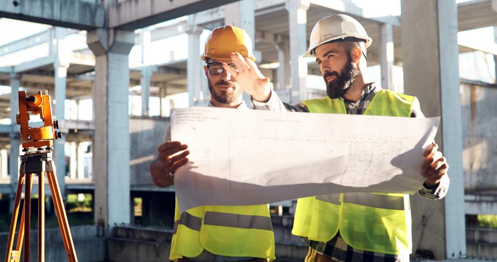 geodeci czytający mapę na budowie